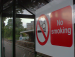 A No Smoking sign on a shelter at Halesworth with the station canopy in the reflection