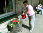 Annette waters the flowers at Darsham Station