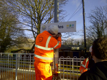 Putting the finishing touches on new signage at Beccles station