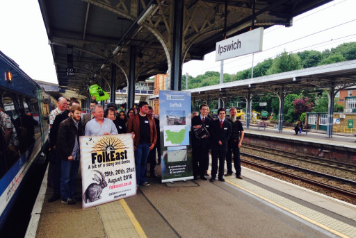 Members of FolkEast, the Young'uns, and the East Suffolk Lines Community Rail Partnership launch the FolkEast Festival and rail-bus link at Ipswich station. A member of staff from Abellio Greater Anglia tries his hand on the melodion!