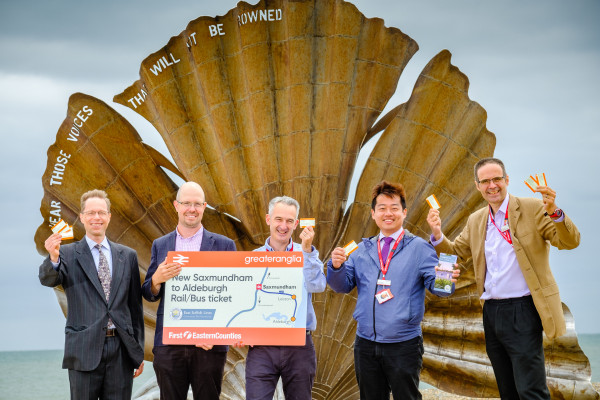 Members of the East Suffolk Lines Community Rail Partnership and representatives from First Eastern Counties and Greater Anglia launch the new Aldeburgh rail/bus through ticket in front of the scallop at Aldeburgh beach
