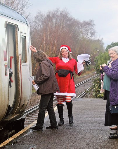 Claire Kendall greets passengers boarding the festive train at Wickham Market station.