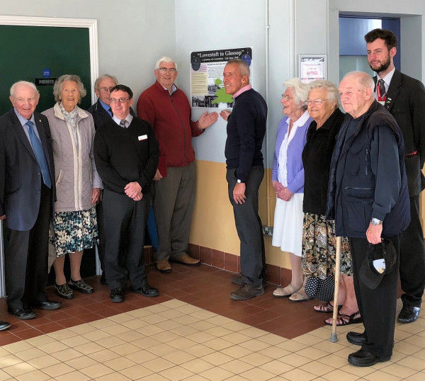 Members from the Lowestoft Evacuees Association, the Friends of Glossop Station along with the High Peak and Hope Valley Community Rail Partnership and Greater Anglia staff in front of the new panel.