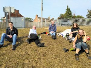 Volunteers take a break after clearing the wildflower patch at Derby Road station